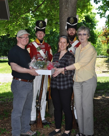 Sgt. Jonah Ellens & Corporal Jeffery Parent of the 100th Regiment of Foot (Reenacted) stand at attention while Museum Chairperson Ken Cownley, left, and Vice-Chairperson Linda Preston, right, present Kathryn Jamieson with a parting gift.