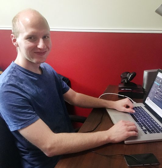 Jonah Ellens with a laptop in his home office.